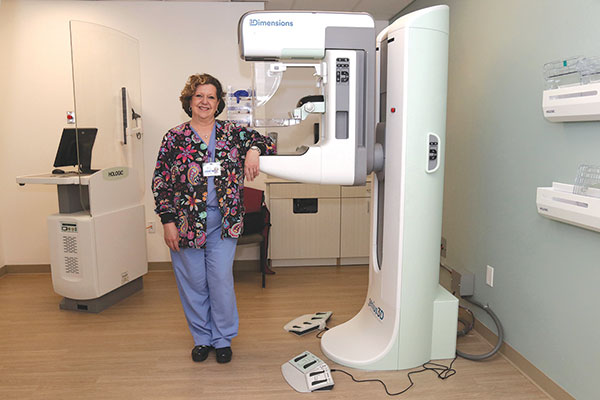 Friendly technician standing next to mammography machine