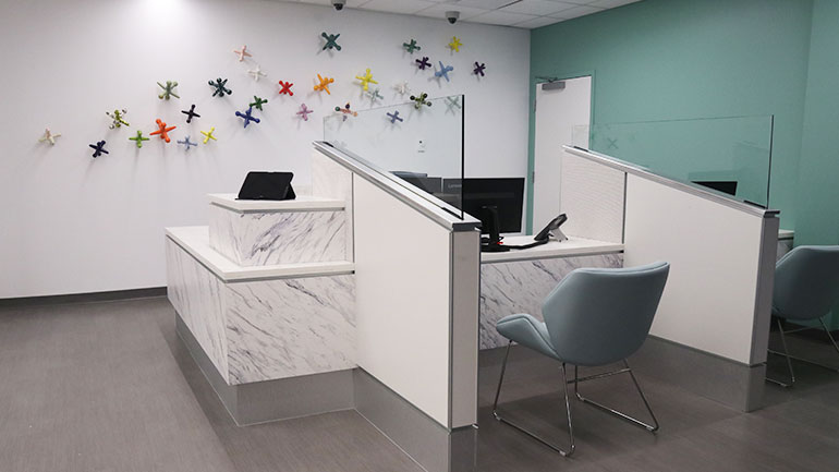 Waiting room with registration desk and large colorful jacks on the wall