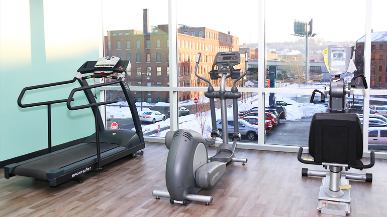 Exercise machines next to a large window overlooking the city