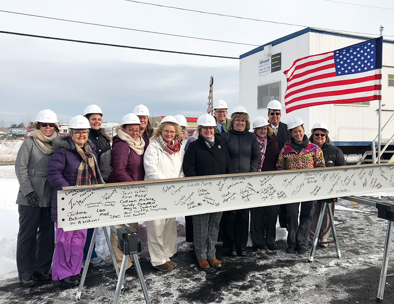 Group of employees wearing hard hats standing behind a plank covered in signatures
