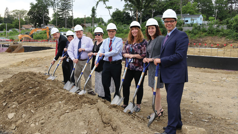 Group of Reliant executives wearing hard hats holding shovels