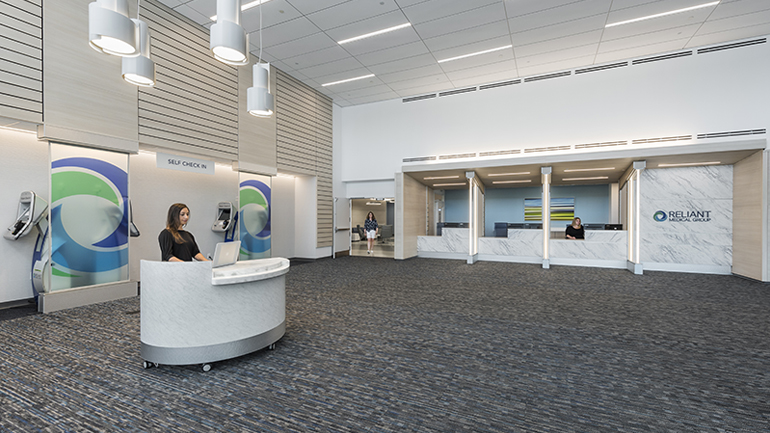 Lobby with a person sitting at a small desk