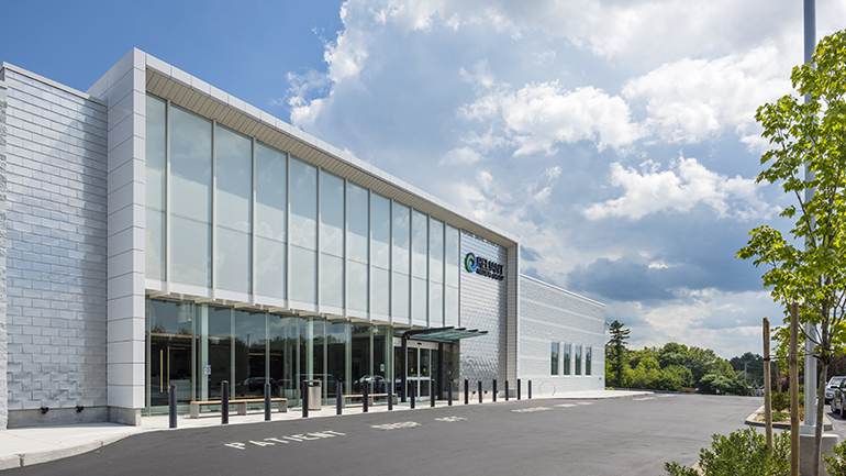 Exterior of a large glass sided building on a sunny day