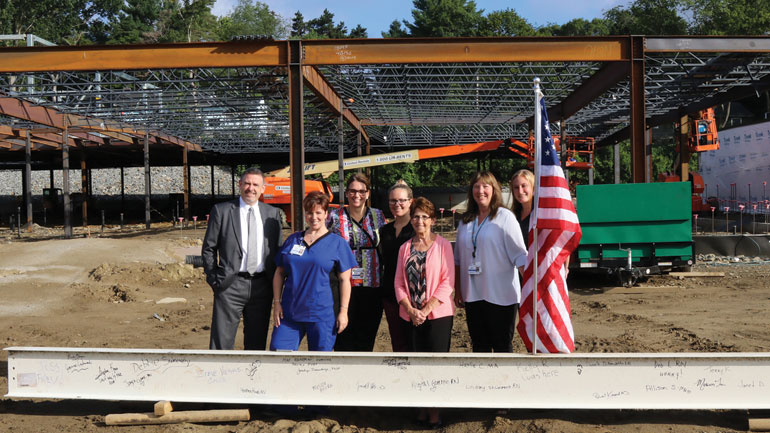 Group of Reliant employees standing in front of a signed beam