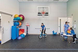 Gym with basketball hoop and colorful physical therapy balls