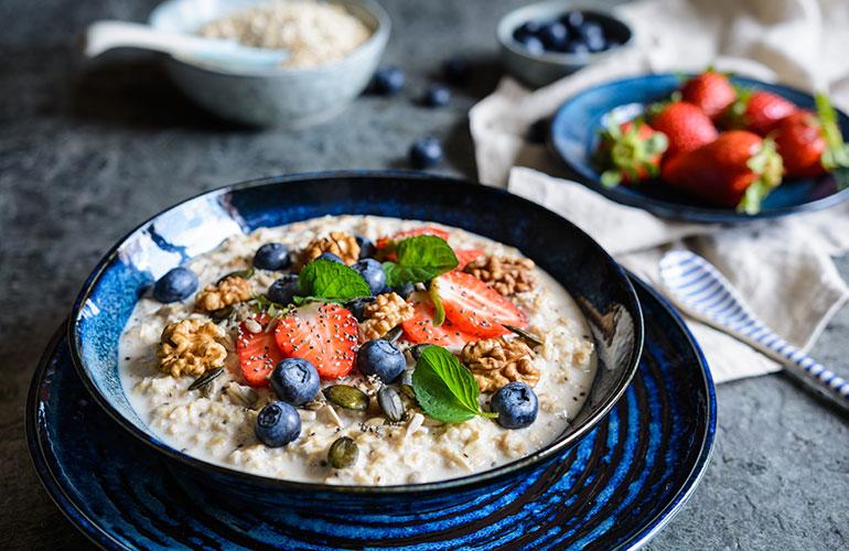 Nutritious Bircher muesli with strawberries, blueberries, chia seeds, walnuts, sunflower seeds and pumpkin seeds