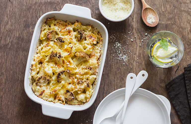 Cauliflower mac and cheese on the brown wooden table, top view
