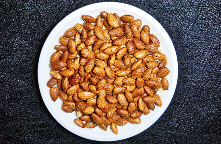 Fried and spiced almond nuts in white plate on dark background