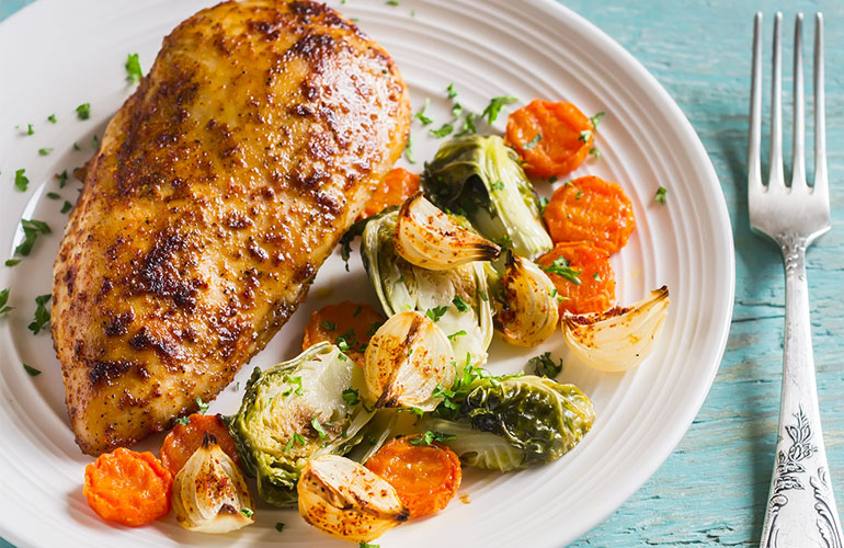 baked chicken breast with brussels sprouts, onions and carrots on a white plate on wooden surface