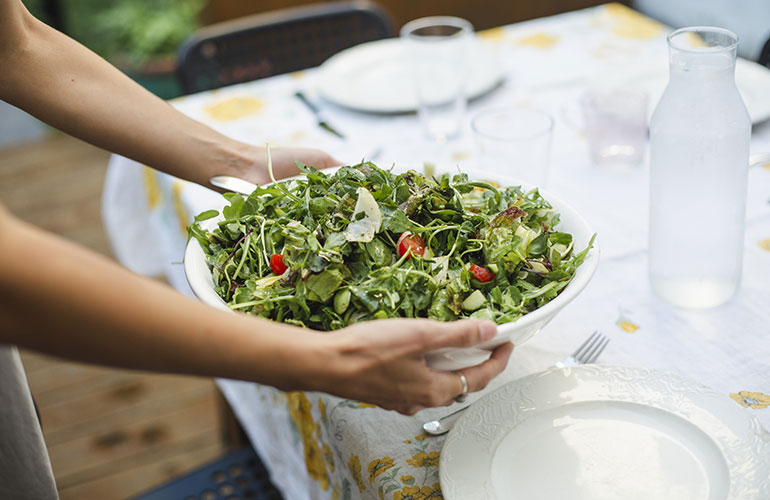 person holding a green salad over a table